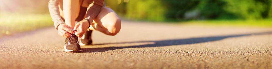 Fototapeta Young woman running in the park on asphalt road obraz