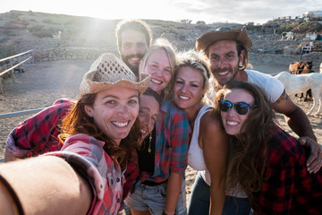 group of seven people together having fun in a ranch with horses - caucasian people taking a selfie smiling and laughing togetherness - enjoying