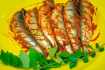 Sardines marinated with chilli masala ready for frying garnished with curry leaves in a a yellow plate.