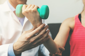 physiotherapy - physiotherapist help woman patient to recover from hand injury at home. dumbbell exercises