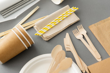 recycling, tableware and eco friendly concept - disposable dishes of paper and wood on grey background