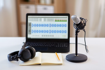 post production and technology concept - microphone, laptop computer with sound editor program,...