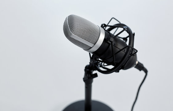 technology and audio equipment concept - close up of microphone on white background