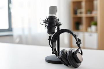 technology and audio equipment concept - headphones and microphone at home office or recording studio