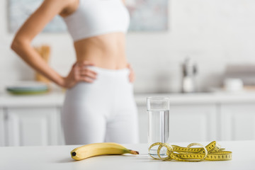 Selective focus of banana, glass of water and measuring tape on table near sportswoman in kitchen