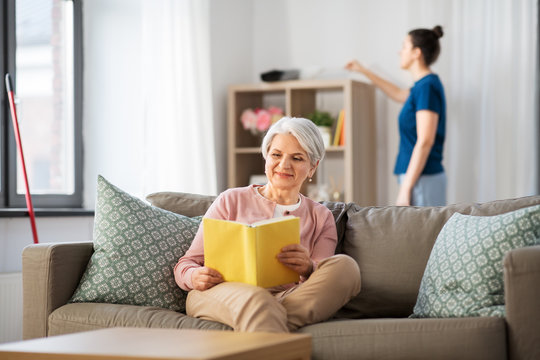 leisure, old age and people concept - happy senior woman reading book and housekeeper cleaning at home