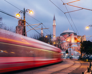 Istanbul, Turkey - Jan 9, 2020: A T1 tram passes the Hagia Sophia museum at dusk, Istanbul, Turkey