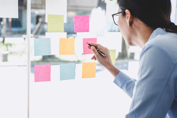 Business woman leader working marketing growth on financial document graph report statistics, using post it notes in glass wall to writing strategy business plan to development grow to success