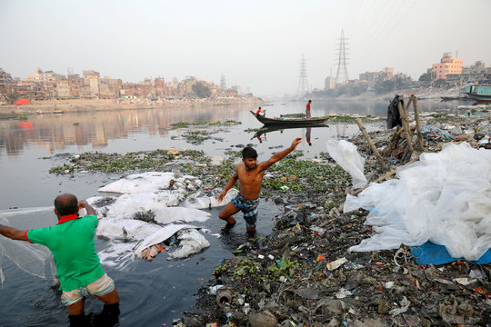 Men wash plastic waste in waters of the Buriganga River before recycling it, in Dhaka