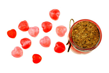 Red heart shaped lollipops together in glass bottle on white background