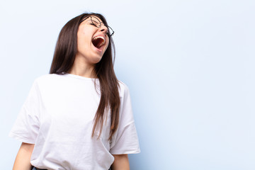young pretty woman screaming furiously, shouting aggressively, looking stressed and angry