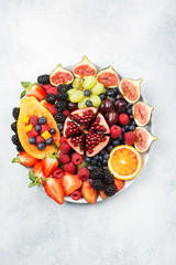 Delicious fruit platter mango papaya oranges figs berries on round serving plate on off white background, overhead view, selective focus, copy space