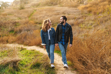Image of beautiful couple dating and walking together in countryside Fotomurales