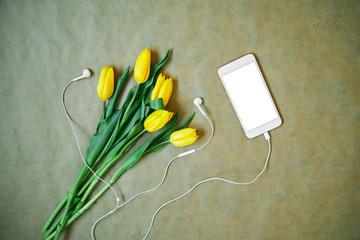 Bunch of yellow tulip flowers and cellphone. Spring/technology concept.