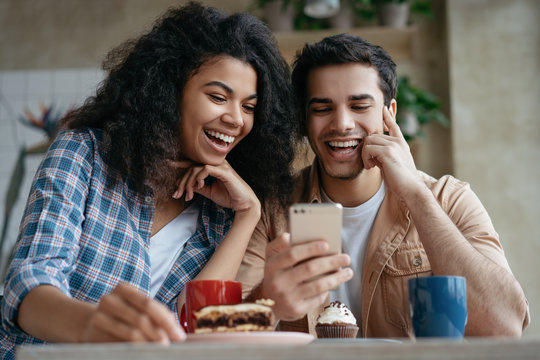 Happy couple using mobile phone and internet, watching movie together, communication, laughing, sitting in cafe. Positive hipster friends shopping online, looking at digital screen