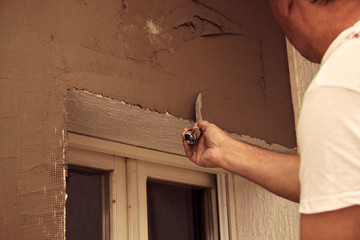 Construction worker plaster a wall.