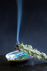 White sage smudge stick on dark background. Burning / smudging sage on abalone shell. Native American tradition for cleansing negative energy.