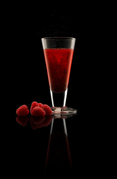 Whisky Rasberry Shrub cocktail with fruit on black background.
