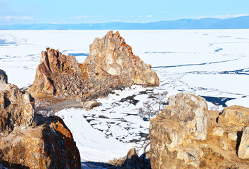A magnificent sunny landscape of early spring on Baikal Lake. View from Cape Burhan to the famous Shamanka Rock on the April morning. The destruction of ice on the Small Sea Strait. Natural background