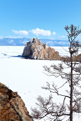 Baikal Lake and Olkhon Island in early spring. A magnificent sunny landscape with the famous Shamanka Rock against the background of crumbling ice cover in the Small Sea