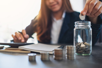 Closeup image of a businesswoman stacking and putting coins in a glass jar