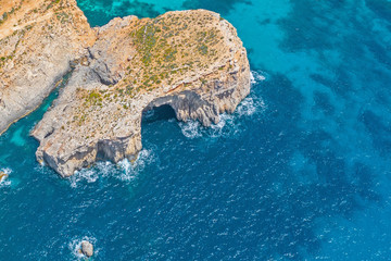 A rock with an arch cave in the blue azure sea, aerial view.