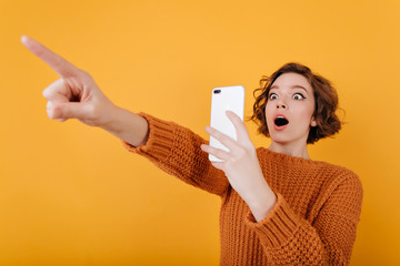 Surprised pale girl with surprised face taking picture of someone. Indoor portrait of amazed young woman in sweater using phone for photo.