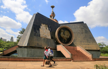 People walk past the Italian marbled Nyayo monument erected in 1988 by the Kanu regime to honour former president Daniel arap Moi, at the Central Park in Nairobi