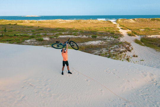 Mountain biker rides in the high sand dunes close to the sea side.