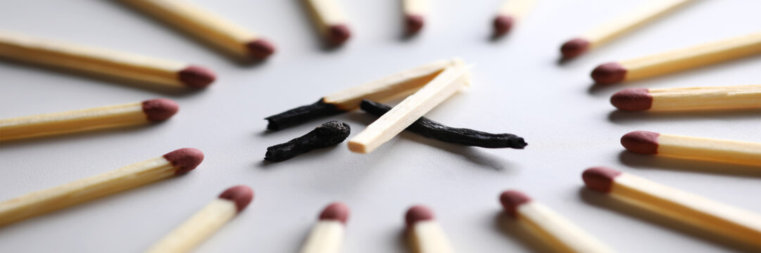 Broken burned out match in surrounded by evil intact fellows
