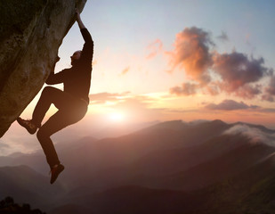 Rock climbing. Young male risky climber trying staying on challenging cliff route. Scenic mountain landscape with sunrise sky on background. Fail, difficulties, overcoming obstacles. Copy space
