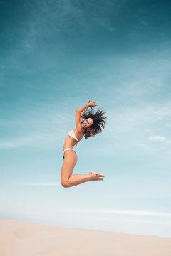 Young woman in bikini jumping over sand