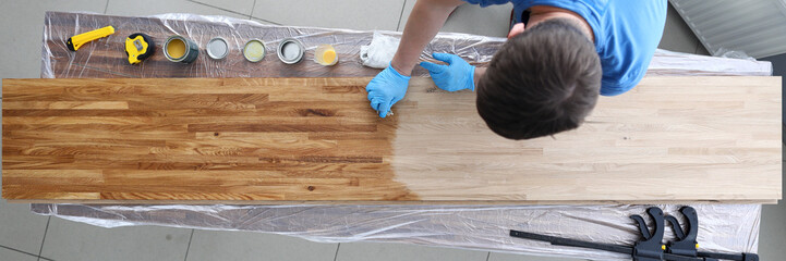 Top view of handy man covering wooden desk with oil