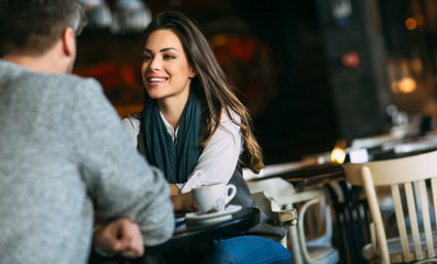 Young couple at the bar having a coffee and flirting Fotobehang