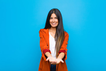 young pretty latin woman smiling happily with friendly, confident, positive look, offering and showing an object or concept against flat wall Wall mural