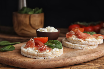 Puffed rice cakes with prosciutto, tomato and basil on wooden board