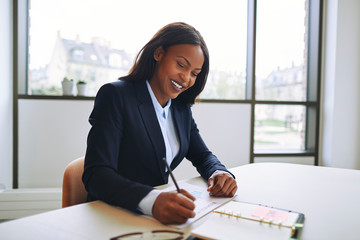 Smiling African American businesswoman writing notes at an offic