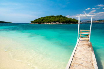 Paradise beach with wooden pier in Ksamil in  Albania