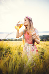 Woman in traditional clothing drinking beer in Bavaria