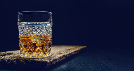 Stores photo Alcool glass of whiskey with ice on a wooden table surrounded by smoke