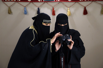 Saudi women look at the pictures displayed in a camera screen during Tantora festival, in the old town of al-Ula
