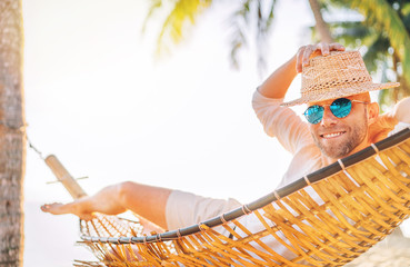 Young man in straw hat and blue sunglasses  lying swinging in cozy hammock sincerely smiling meeting morning sunrise sunlight on beach under the palm trees. Calm exotic places vacation concept image.