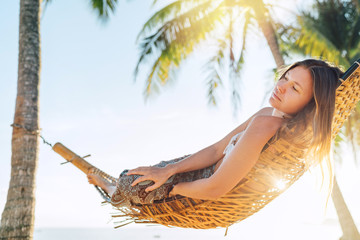 Lost in dreams Young woman swinging in cozy hammock meeting morning sunrise sunlight lying  in a hammock on the sandy beach under the palm trees. Calm exotic places vacation concept image.