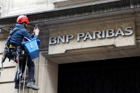 A worker cleans up the facade of a BNP Paribas bank office in Paris