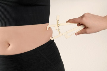 Nutritionist measuring woman's body fat layer with caliper on beige background, closeup