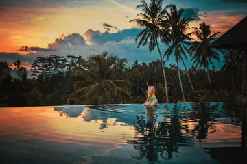 Autocollant pour porte Bali Woman relaxes in a luxury infinity pool overlooking the jungle at sunset in Ubud, Bali. A girl sits on the edge of the infinity pool against the backdrop of a bright beautiful sunset and the jungle.