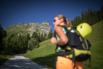 Pretty, female climber on a via ferrata -  climbing on a rock in Swiss Alps - Approach phase