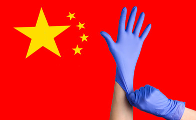 Outbreak Coronavirus epidemic in China. Medic's hands put on gloves on the background of the flag of China
