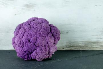purple cauliflower lying on a gray slate plate