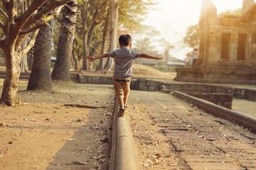 An Asian boy is enjoying his balance.